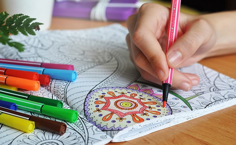 Coloring an adult coloring book to relieve stress and get comfortable and calm